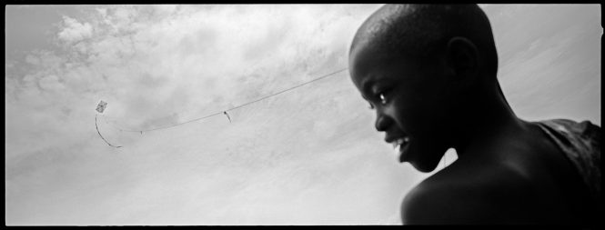A kite made of sticks and a plastic bag flies over a Cap Haitien, Haiti slum with the innocence and hope of the boy who made it from matierials he found in the garbage.