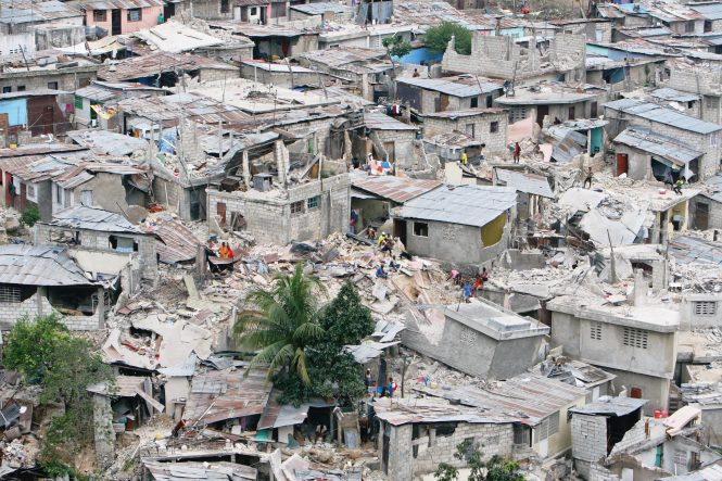 A neighboorhood in the Petionville area of Port-au-Prince, Haiti lies in ruins as people pick through what remains after the earthquake.