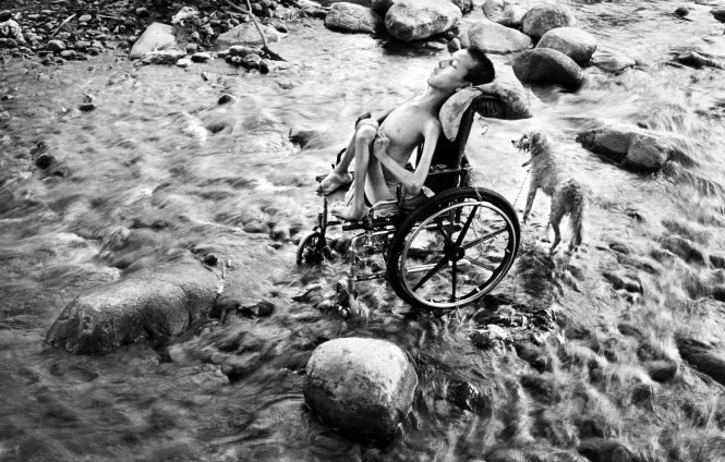 "With his limbs twisted and crippled since birth, Reynaldo Reyes, 15, waits in a Honduran stream for his mother to bathe him after she washes laundry downstream to earn money for the family. Maria Reyes says she pushes Reynaldo with a laundry basket tied to his wheelchair  2 miles over rocky roads and embankments because she fears leaving him home alone.  She says of the dog, ""That is Reynaldo's best friend. They are  together every day, and they are never apart."" 2003"