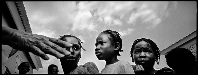 A trio of girls anxiously waits in line for food at a relief agency distribution near Port-au-Prince, Haiti.