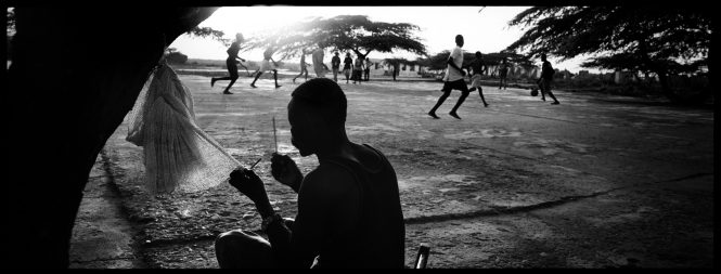 Hopeful for tomorrow, men repair their nets after a day of fruitless fishing while others play soccer in a coastal village in northern Haiti.