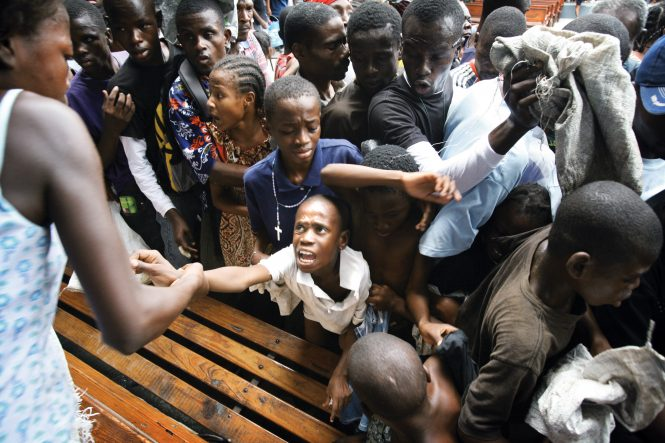 Thousands of desperately hungry earthquake victims clamor for food as Food For The Poor and the Salvation Army distribute a tractor trailer of food at the Salvation Army compound in Port-au-Prince, Haiti. The crowd, near their boiling point, pressed together dangerously.