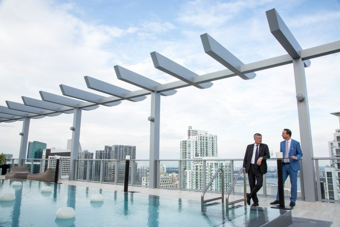 Paolo Pininfarina, left, chairman of the Italian design firm Pininfarina and Mateo De Lise, managing director at Pininfarina of America Corp look at the Miami skyline from the rooftop pool of 100 Millecento of the newly completed building. The Italian design firm Pininfarina, famous for designing expensive cars like Ferraris, has moved into architecture with it's first US development project in Miami's Brickell district. 1100 Millecento is a newly completed 43-story, 382-unit condominium with two pools, including one on the roof, a fitness center, business center, billiard room, lounge, library, children's playroom and it's own small movie theater. Photograph for the New York Times by Benjamin Rusnak