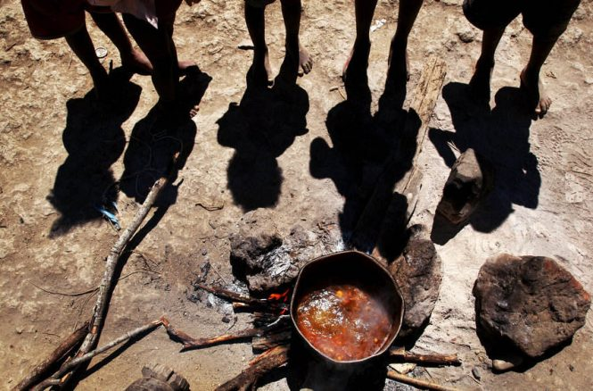 "Anxiously awaiting their only meal of the day, children gather around a meager pot of vegetable broth that needs to feed 5 children and 2 adults. Their grandmother, Mercedes Visiosa, 75, does her best to provide, but says it is out of her hands. ""God gives me my daily bread. My life is his."""