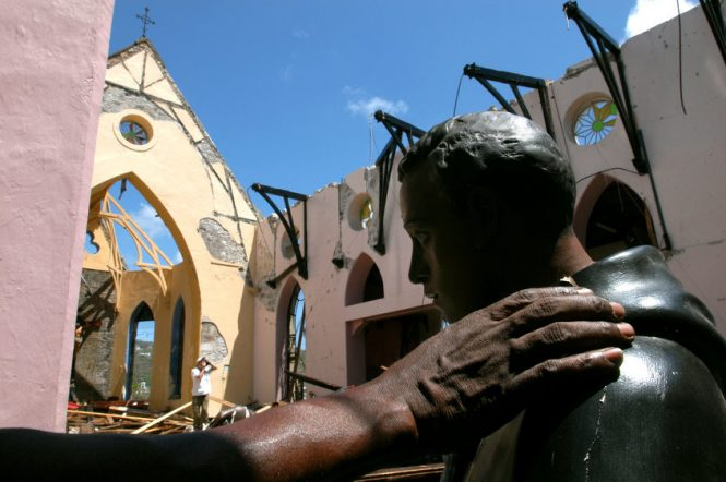 A deacon surveying the damage to the Catholic Cathedral of the Immaculate Conception in St. George's, Grenada touches one of the few things to survive Hurricane Ivan's category five winds: a damaged statue of Saint Martin. The hurricane killed dozens and left thousands homeless when it destroyed or damaged 90% of the buildings on the island.
