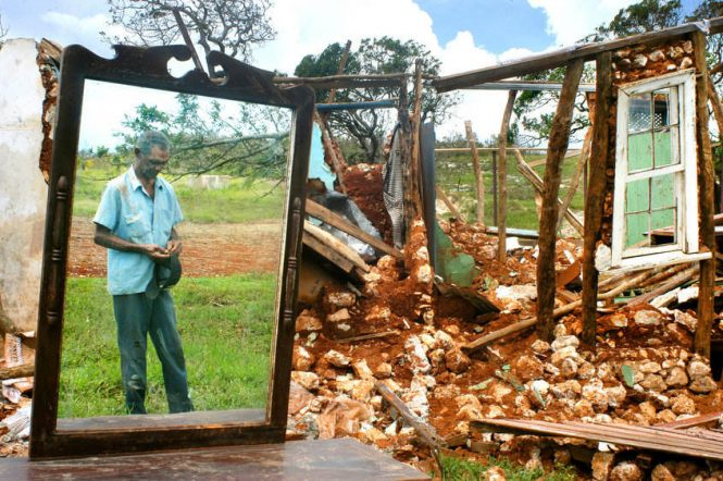 Windall Bent, who didn't know his age, reflects on his demolished home, which survived 100 years and many storms until the category five winds of Hurricane Ivan whipped the south coast of Jamaica.