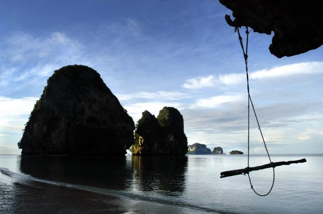 Awaiting both the high season and the high tide of the bay is a swing hanging from the jagged limestone cliffs of Railey, Thailand.